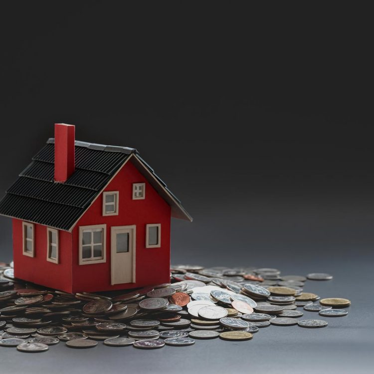 Real estate and property investment concept : small house model on stack of coins with black background